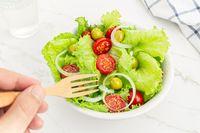 Hand of a man eating a Fresh and healthy salad in a bowl