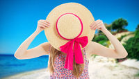 Elegant young lady in summer hat on beach vacation