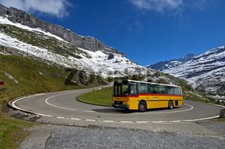 Gelbes Postauto in einer Haarnadelkurve auf der Bergstrasse zum Klausenpass vor den Glarner Alpen bei Urnerboden