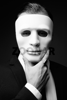 Young businessman against gray background in black and white