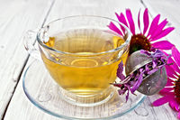 Tea Echinacea in glass cup with strainer on board