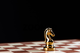 Golden knight chess figure on chessboard