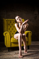 Young beautiful, sexy Caucasian woman with a thin figure and long bare legs, barefoot posing sitting on a yellow chair in the interior against a dark wooden wall. Dressed in black classic underwear