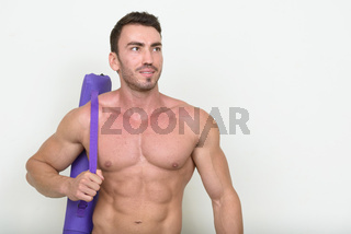 Portrait of handsome muscular bearded man shirtless and ready for gym