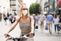 Woman riding bicycle on city street wearing medical face mask in public to prevent spreading of corona virus. New normal during covid epidemic.