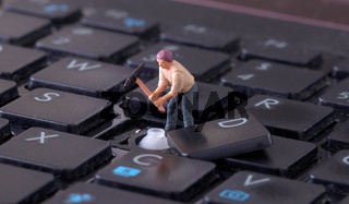 Miniature worker with pickaxe working on keyboard