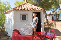 Woman on summer vacation in front of unique vintage traditional mobile home house at camping site, relaxing and enjoy pure Mediterranean nature on holiday trip on Sardigna island, Italy
