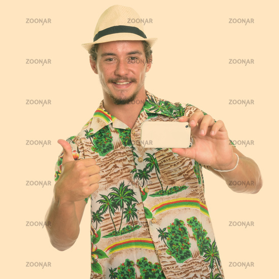 Studio shot of young happy tourist man smiling while taking picture with mobile phone and giving thumb up isolated against white background