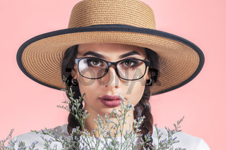 Studio fashion portrait of beautiful young modern fashionable woman with wild flowers