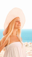 Woman with blond hair wearing hat, enjoying seaside and beach lifestyle in summertime, holiday travel and leisure