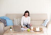 Female freelancer using smartphone at home