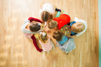 Group of children playing educational cards on a floor. Puzzle with animals mother and baby.