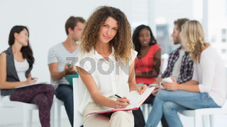 Pretty woman smiling at camera while colleagues are talking behind her