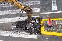 Construction Machine jackhammer breaking asphalt of the road