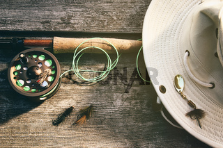 Fly fishing rod with hat on wood
