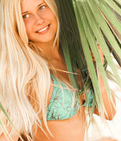 Woman with blond hair wearing bikini, posing near palm tree, beach lifestyle in summertime, holiday travel and leisure