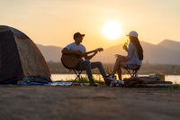 Asian couple with dog playing guitar and drinking beer beside their tent campsite