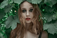 Portrait of beautiful young woman staying in front of green leaves