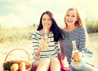 girlfriends with bottles of beer on the beach