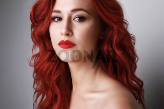 Headshot of young woman with beautiful long red hair posing over white wall.