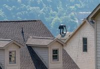 Young roofing contractor nailing shingles on a roof high above the ground