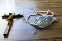 A crucifix and a mouth mask on a wooden table in the sunlight