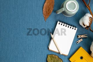 Work and study place. Winter concept. Notebook and pencil, mug cup, dry plant on blue fabric background. flat lay, top view, copy space