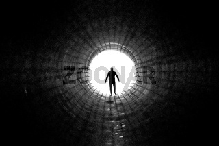 Silhouette of a man walking to the light at the end of a big tunnel. Concept of escape, exit, freedom, clinical death