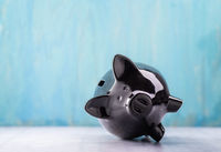 Black piggy bank lies on its side