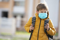 A masked child goes to school after being quarantined and isolated from the coronavirus.