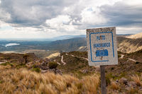 Rusty sign of viewpoint in Gold's Road, San Luis, Argentina, which climbs steppe mountains with curved ascending ways