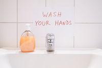 wash your hands handwritten notice above bathroom sink