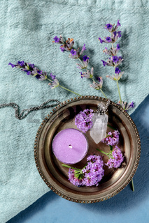 Botanical preparations. Perfume vial and scented candle, lavender and vervain flowers, shot from above
