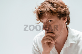 Handsome thoughtful young hipster man, isolated on white background, staring into the distance. Copy space at left