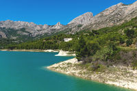 Dam reserevoir lake surrounded by rocky mountains and green forest at Guadalest, Costa Blanca, Spain