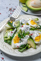 Spinach salad with avocado, cucumber and egg.