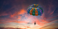 Two people enjoy parasailing flight during sunset bright colorful sky background