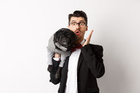 Surprised and amazed dog owner in suit staring at camera, holding cute black pug on shoulder, pet wearing costume, posing over white background