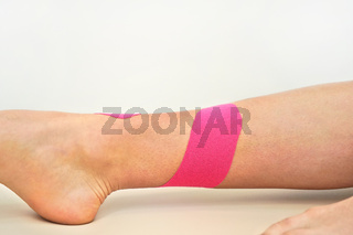 Pink kinesiology tape applied over lower leg and ankle of young female, closeup detail
