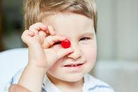 Kleiner Junge hält einen Bonbon in der Hand