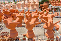 Many orange birds of clay  outside at pottery