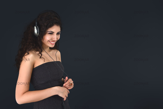 Young beautiful woman portrait listening modern music in headphone isolated over dark gray wide back
