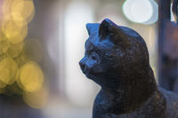 Portrait of a black cast iron cat's head against a blurred light background