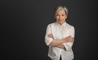 Graying pretty woman in white shirt stands arms-crossed isolated on dark gray background. High quality photo