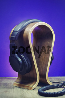 Headphones on a wooden stand as a HIFI music listening icon concept