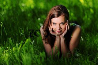 brunette lying on green grass