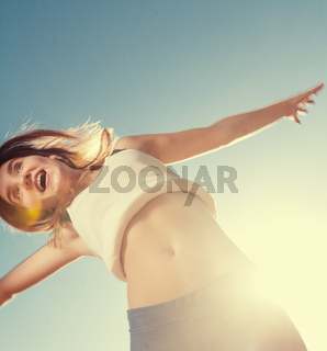 Blonde teenager girl jumping happy with the blue sky in the back