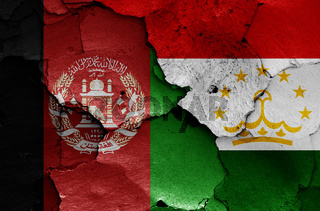 flags of Afghanistan and Tajikistan painted on cracked wall