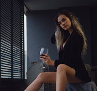 Woman sit on armchair holding glass of red wine pose indoor