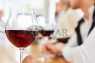 Glas Rotwein im Restaurant vor Gruppe Freunde beim Essen